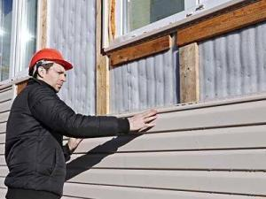 Man fitting cladding to house